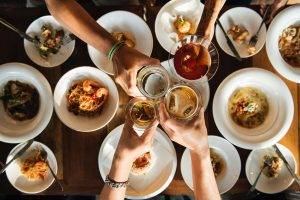 Top down view of a table filled with plates and bowls of food and 4 hands clinking glasses at restaurants in derby